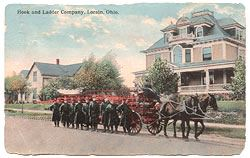 Postcard depicting fire fighters walking along a horse drawn fire wagon